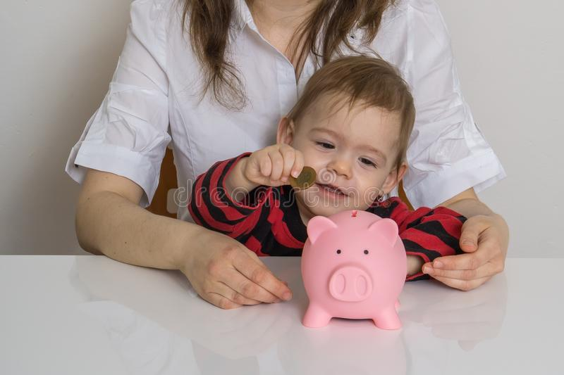 Little girl is putting coins in piggy money bank stock photo