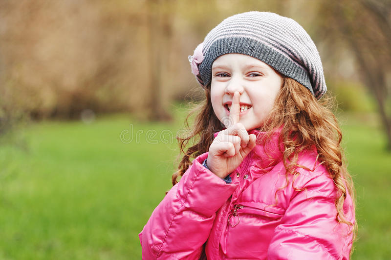 Little girl putting finger up to lips. stock photo
