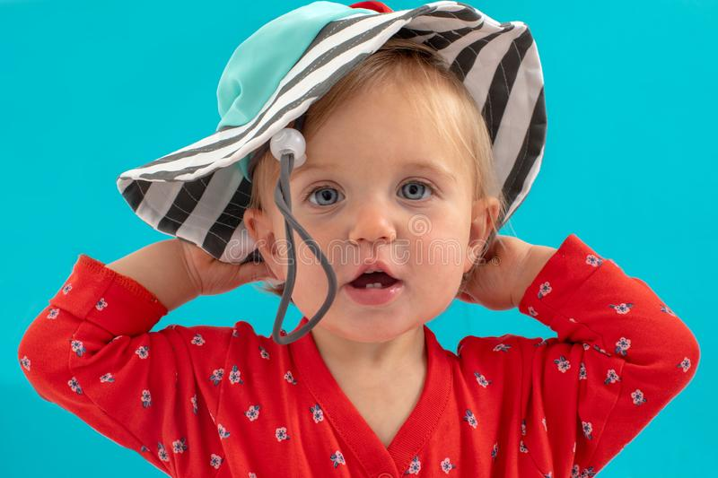Little girl putting on hat over blue royalty free stock photography