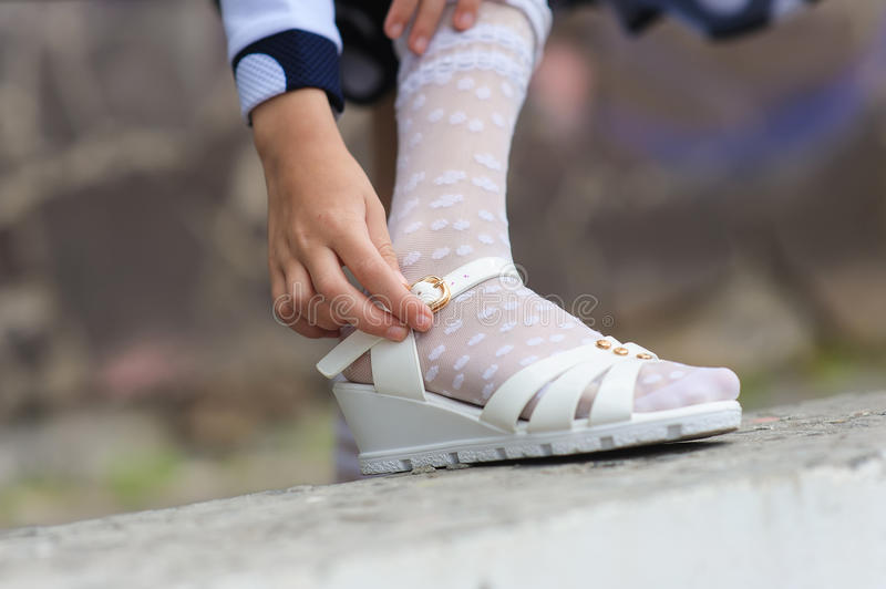 Little girl putting on her sandals. Outdoors stock images