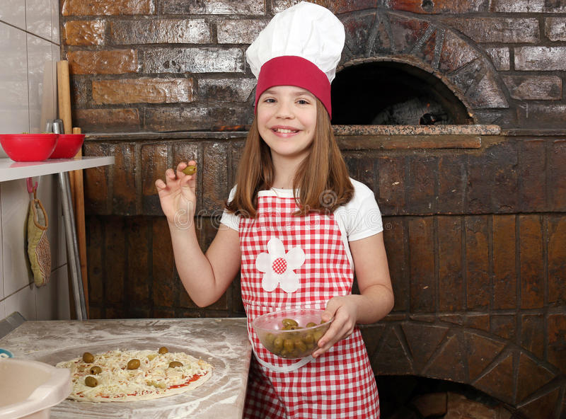 Little girl putting olives on pizza. Little girl cook putting olives on pizza stock photo