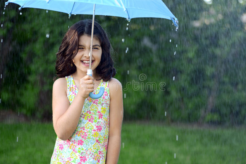 Little girl in the rain. With a blue umbrella stock image