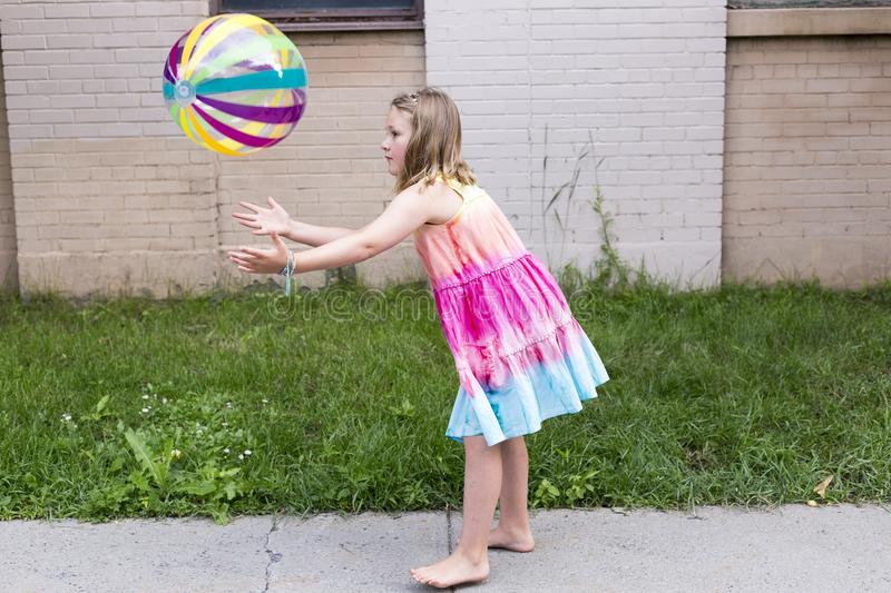 Little girl in rainbow coloured summer dress throwing multicolored beach ball. Pretty barefoot little girl in rainbow coloured summer dress standing in profile royalty free stock images
