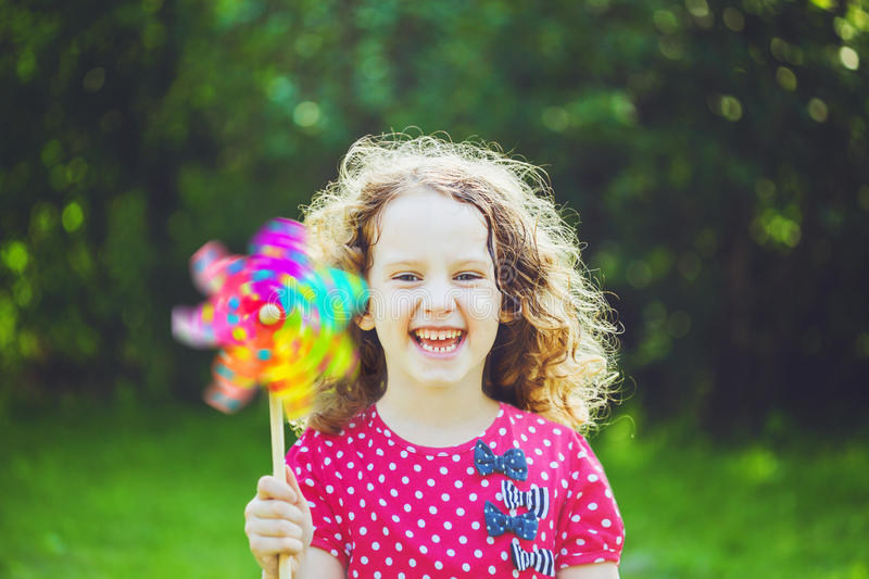Little girl with rainbow pinwheel toy in summer park. Eco, trave stock photos