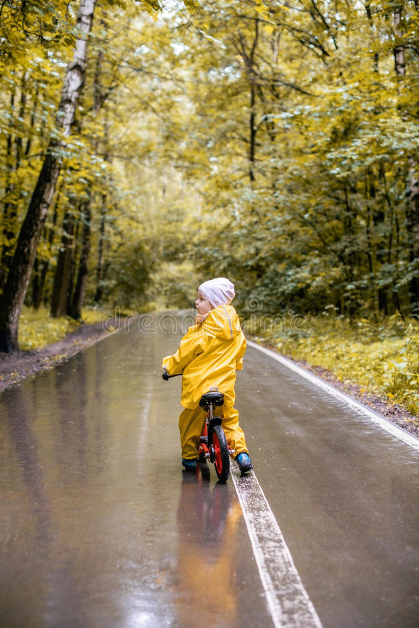 Little girl in rainy day on bike in a park royalty free stock image