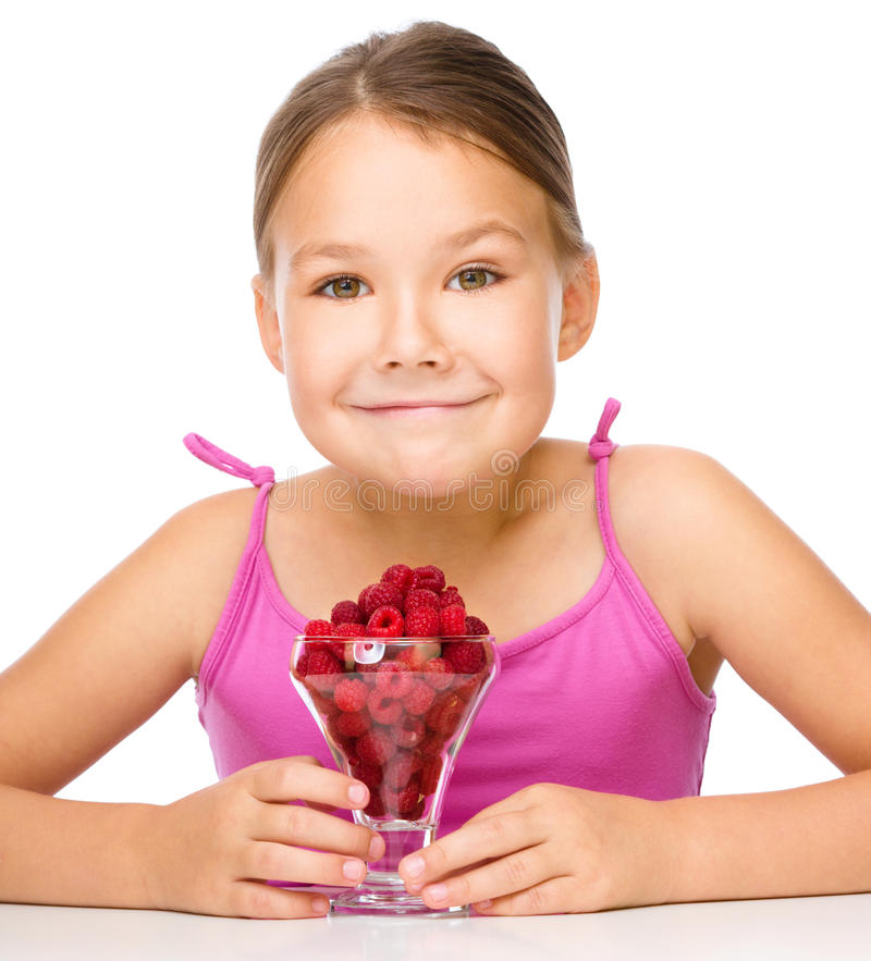 Little girl with raspberries. Little girl is eating raspberries, isolated over white royalty free stock photos