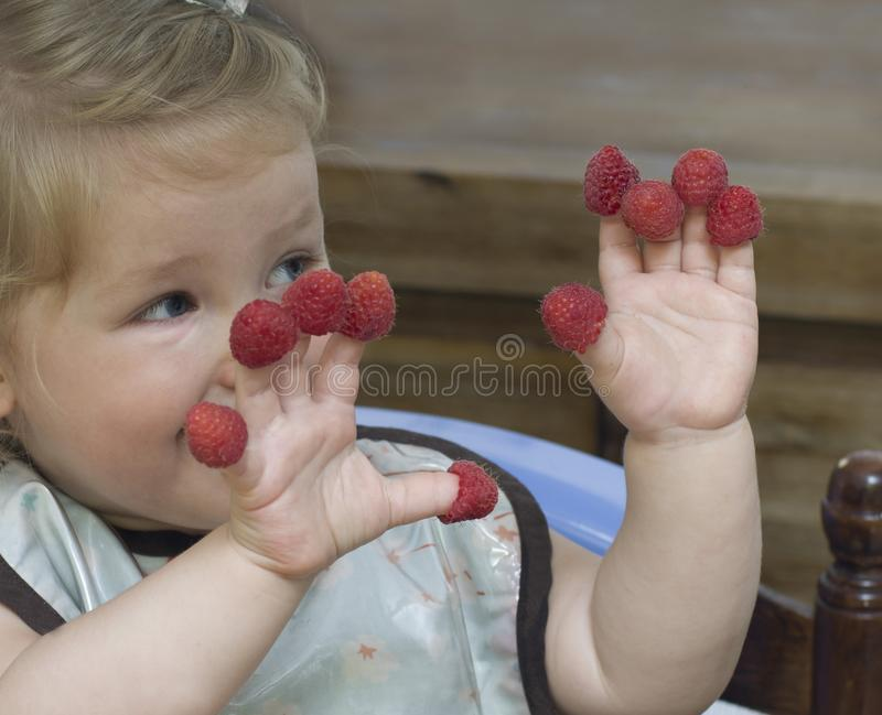 Little girl with raspberry on fingers stock photo