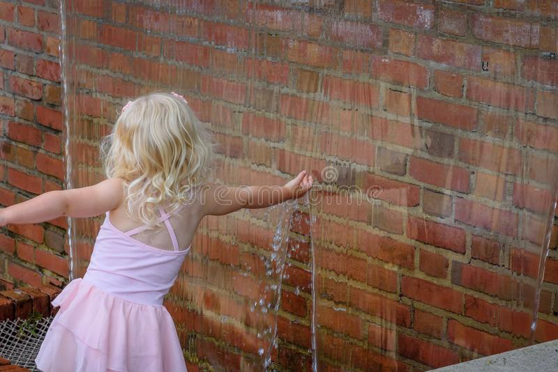 Little girl reaching her hand into waterfall wall touching water royalty free stock photography