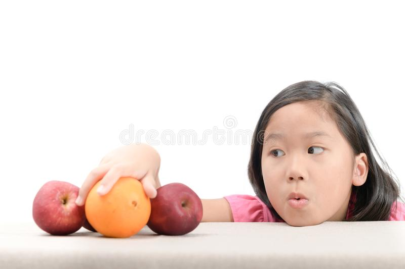 Little girl is reaching orange on table. Cute little asian girl is reaching orange on table on white background, healthy food concept royalty free stock image