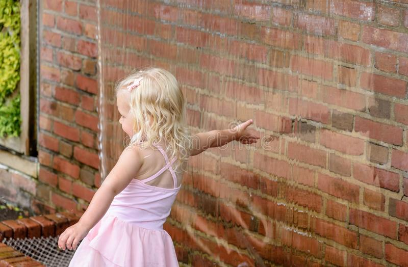 Little girl reaching her hand into waterfall wall touching water stock photos