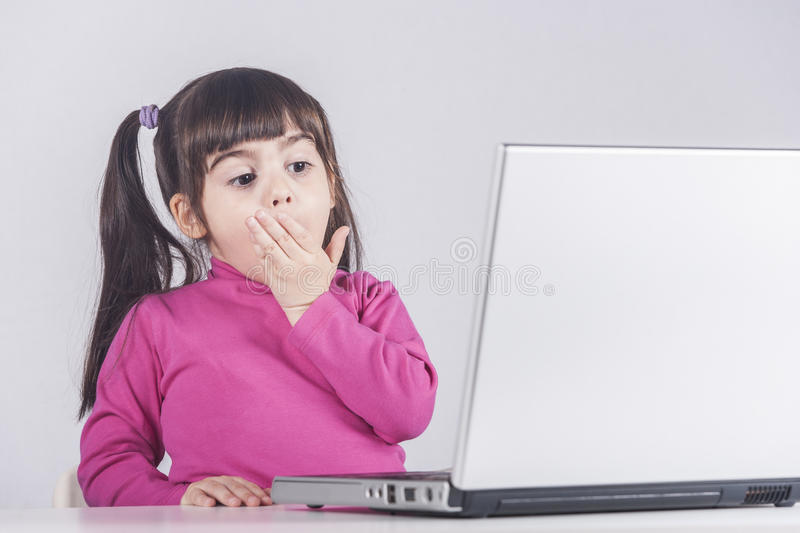 Little girl reacts while using a laptop stock photo