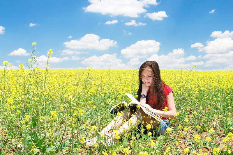 Little girl read book in nature stock photo