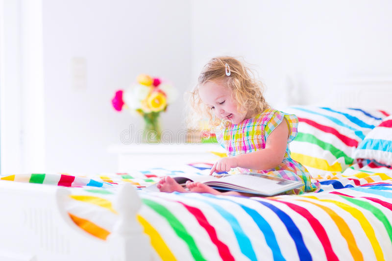 Little girl reading a book in bed. Cute curly little toddler girl reading a book sitting in a sunny bedroom on a wooden white bed with colorful rainbow bedding stock photo