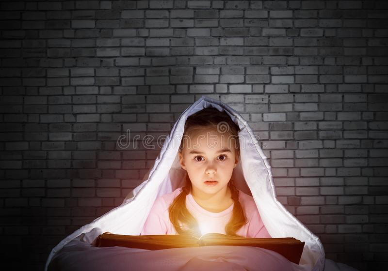Little girl reading book in bed stock image