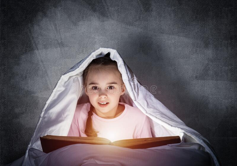 Little girl reading book in bed stock photo