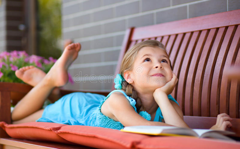 Little girl is reading a book. Cute little girl is reading a book while laying on bench royalty free stock images