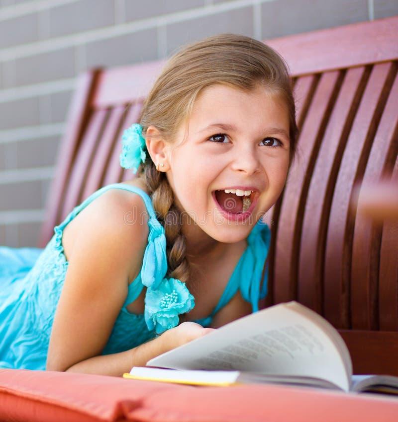Little girl is reading a book. Cute little girl is reading a book while laying on bench royalty free stock photo