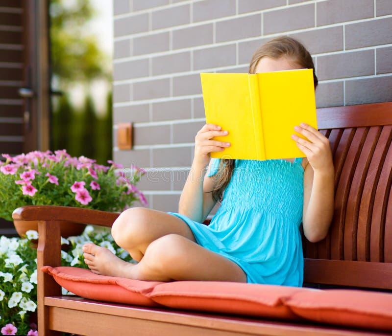 Little girl is reading a book. Cute little girl is reading a book while sitting on bench stock photography