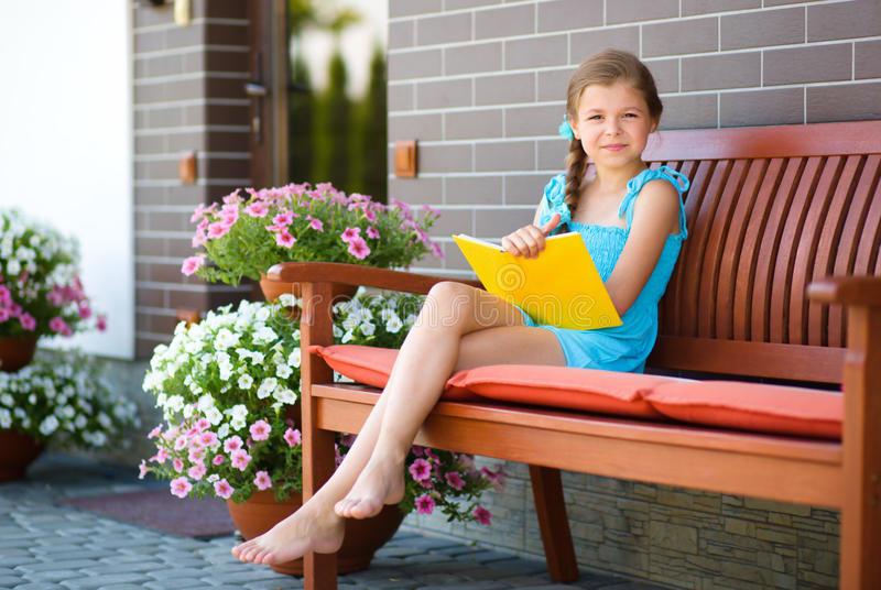 Little girl is reading a book. Cute little girl is reading a book while sitting on bench royalty free stock images