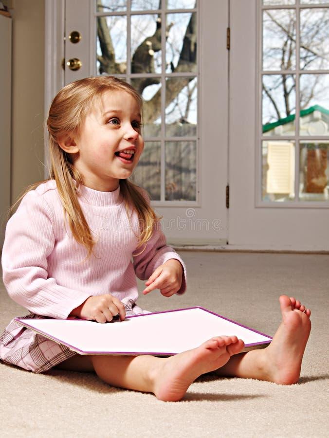A little girl reading a book stock photos