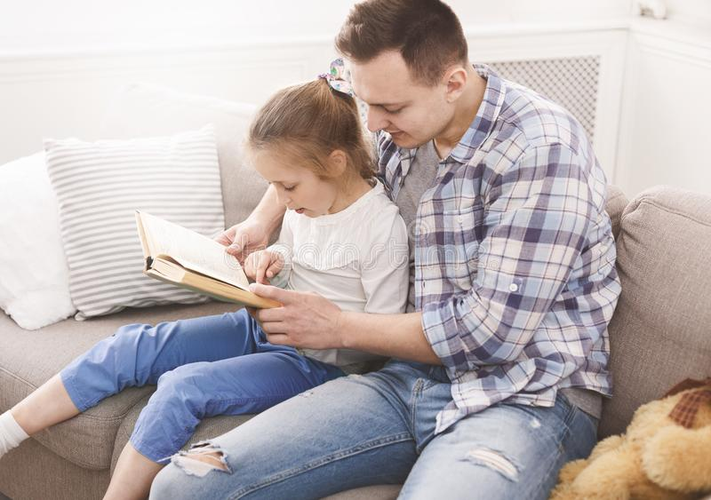 Little girl reading book with her dad royalty free stock photo