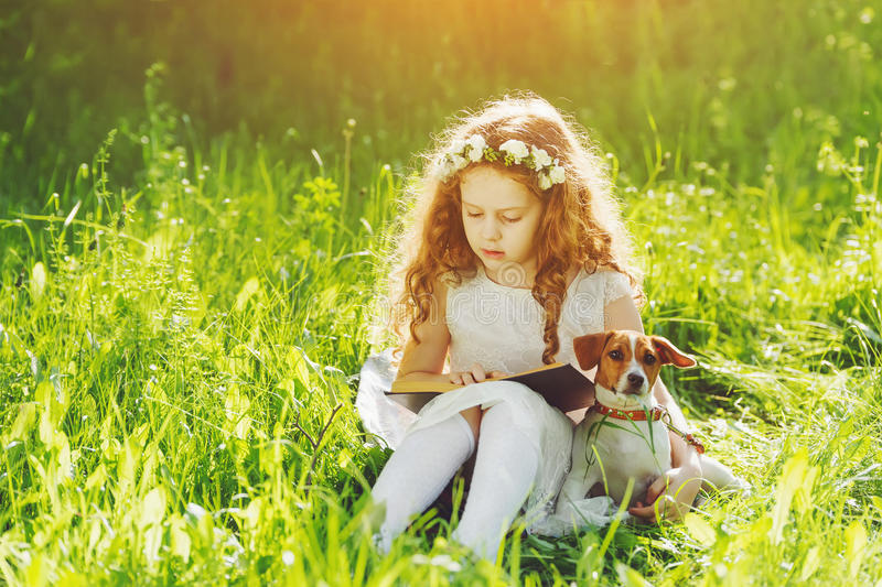Little girl reading a book with her friend puppy dog in the outdoors. royalty free stock photo
