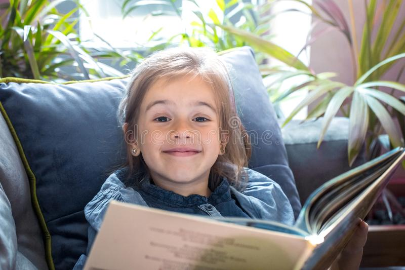 Little girl is reading a book in the living room on the couch stock images