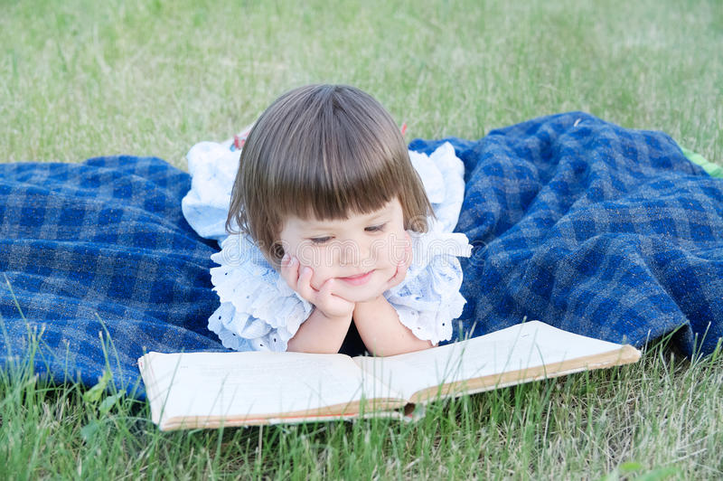 Little girl reading book lying on stomach outdoor, smiling cute child, children education and development. Kids outside activity. stock image