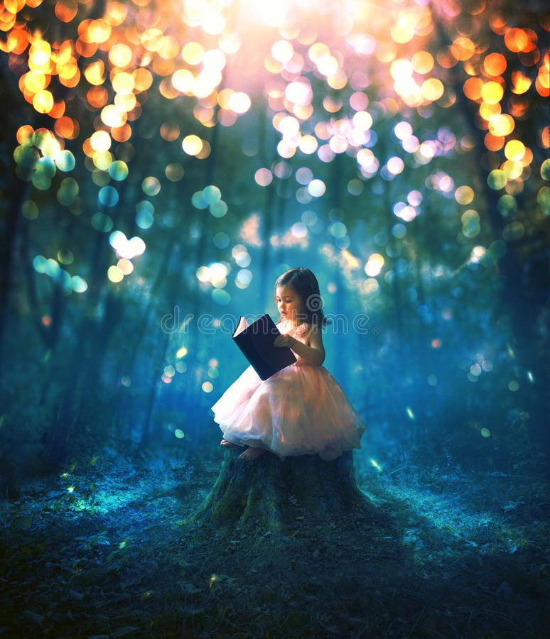 Little girl reading a book. A little girl reading a book in a magical forest stock photos