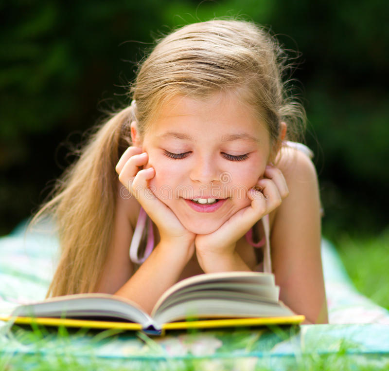 Little girl is reading a book outdoors. Cute little girl is reading a book while laying on green grass stock photography