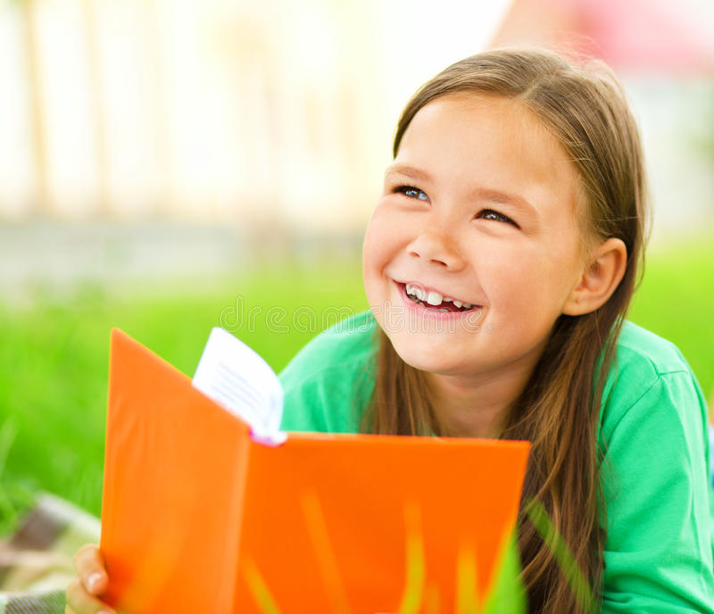 Little girl is reading a book outdoors. Cute little girl is reading a book while laying on green grass royalty free stock photography