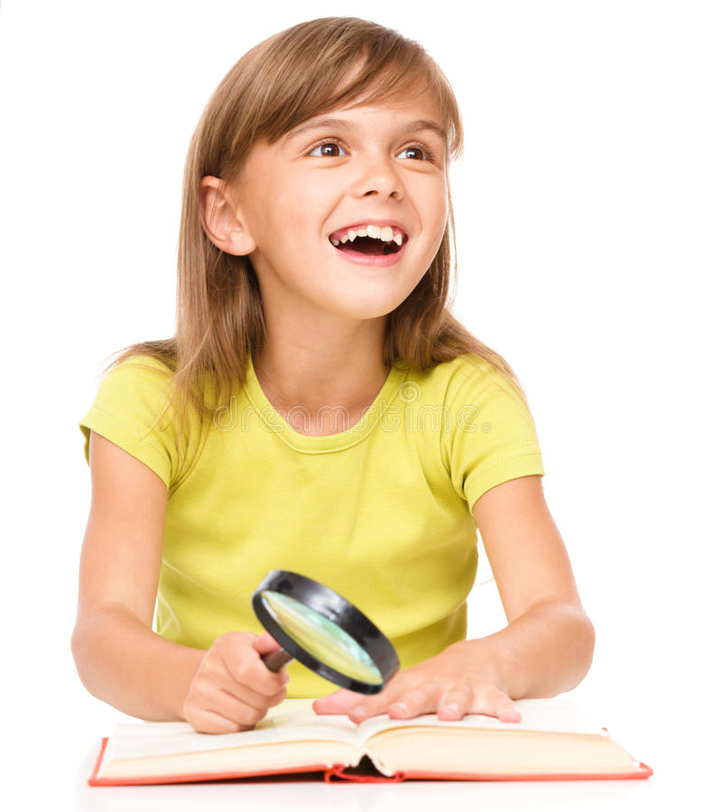 Little girl is reading book. Using magnifier while sitting at table, isolated over white stock photos