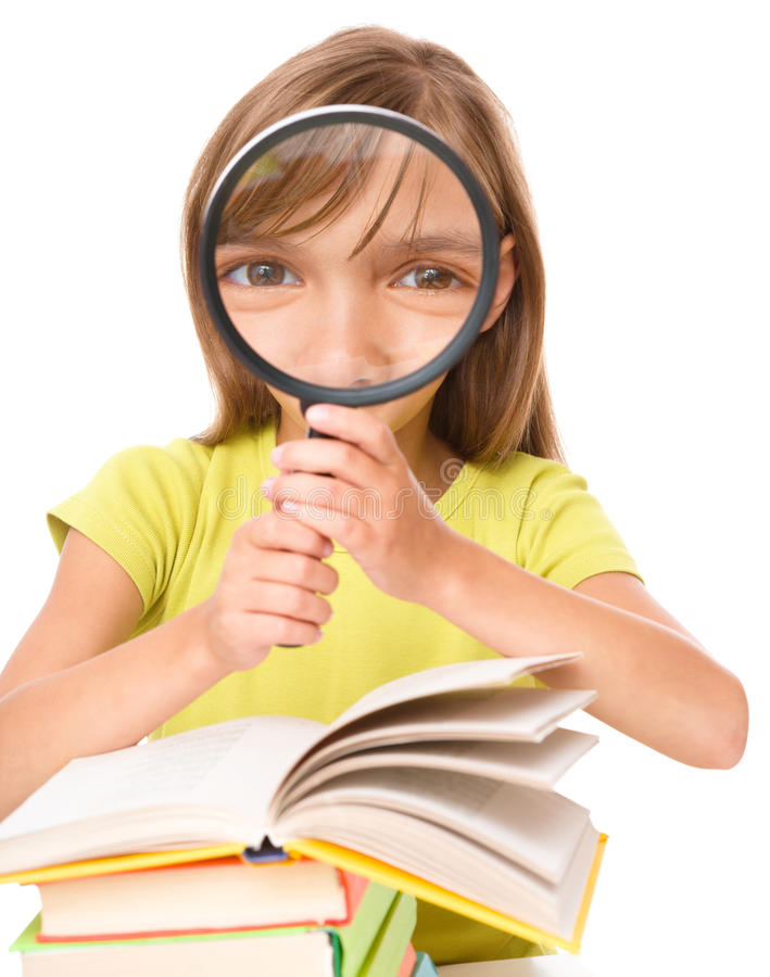 Little girl is reading book. Using magnifier while sitting at table, isolated over white royalty free stock photos