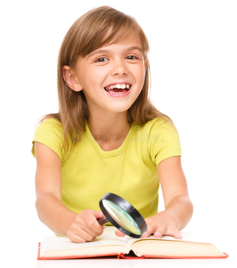 Little girl is reading book. Using magnifier while sitting at table, isolated over white royalty free stock photo
