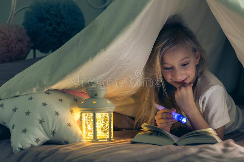 Girl enjoying a book. Little girl reading and enjoying a book at night royalty free stock images