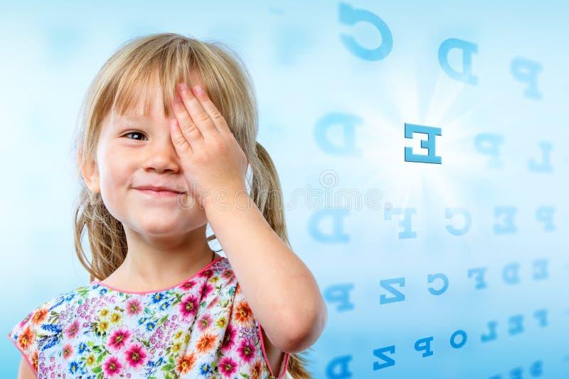 Little girl reading eye chart. stock photography