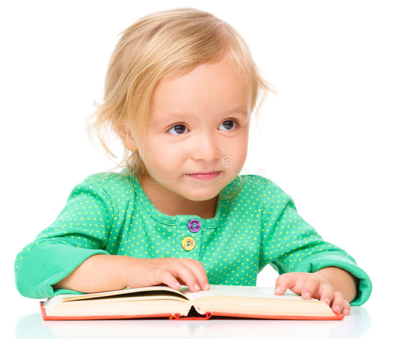 Little girl is reading her book. Isolated over white stock photography