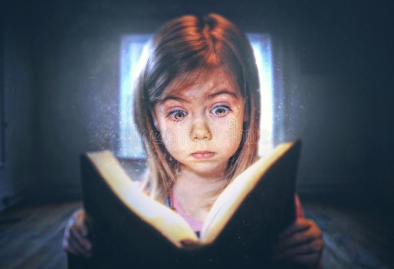 Little girl reading. A little girl reading with a surprised expression royalty free stock photography