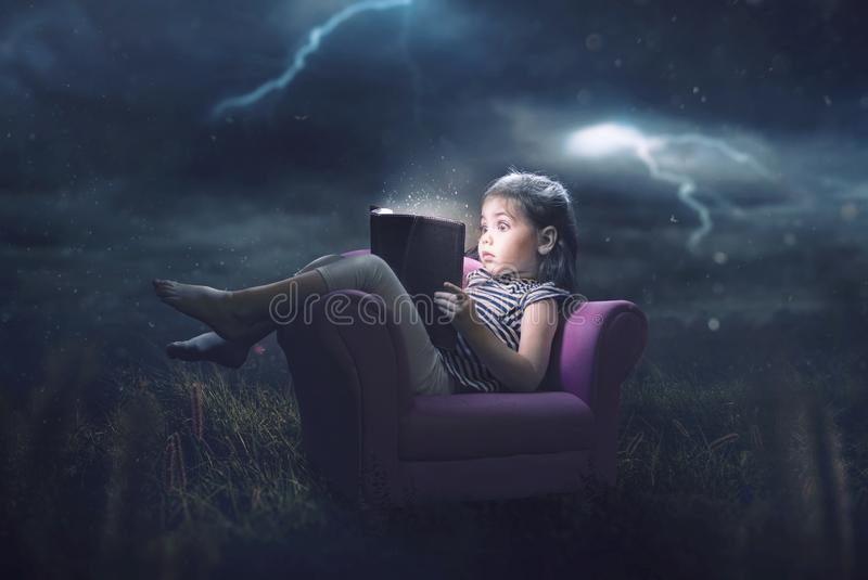 Little girl reading in storm. A little girl is scared and reading during a storm royalty free stock image