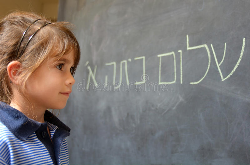 Little girl reads Hello First Grade greetings in Hebrew stock photo
