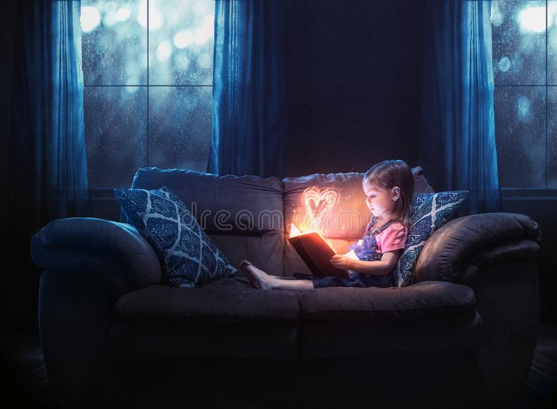 Little girl reads. A little girl reading alone with a color heart glowing out of the pages royalty free stock photo