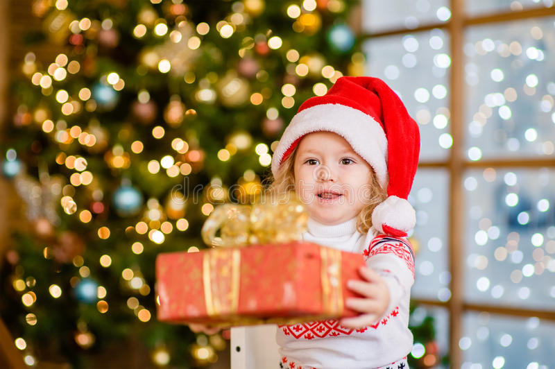 Little girl in a red Christmas hat gives a gift.  stock photos