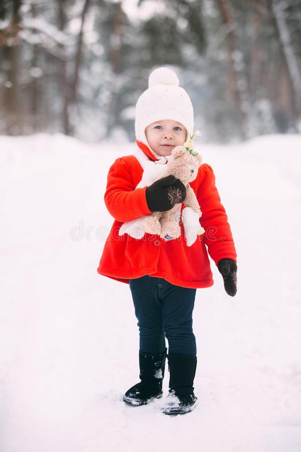 Little girl in red coat with a teddy bear having fun on winter day. girl playing in the snow royalty free stock images