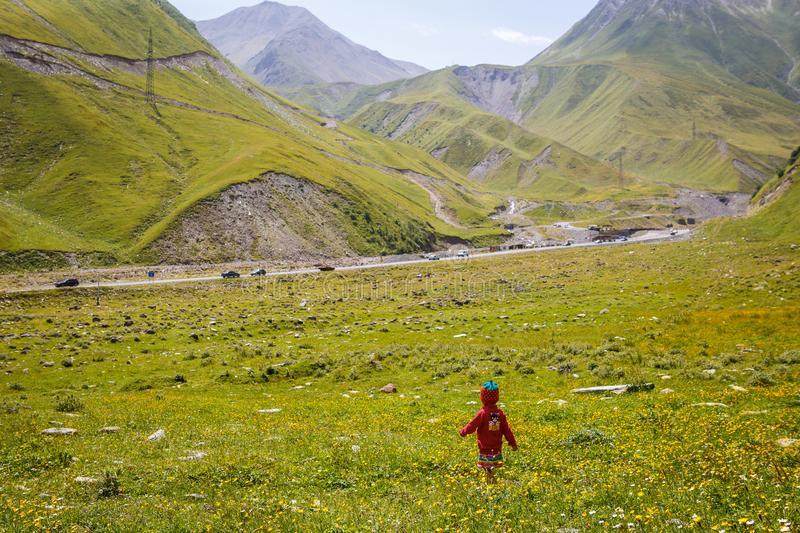 A little girl in a red dress and a knitted cap-strawberry runs on a green field in the mountains. Summer in Georgia, Georgian military road stock photo