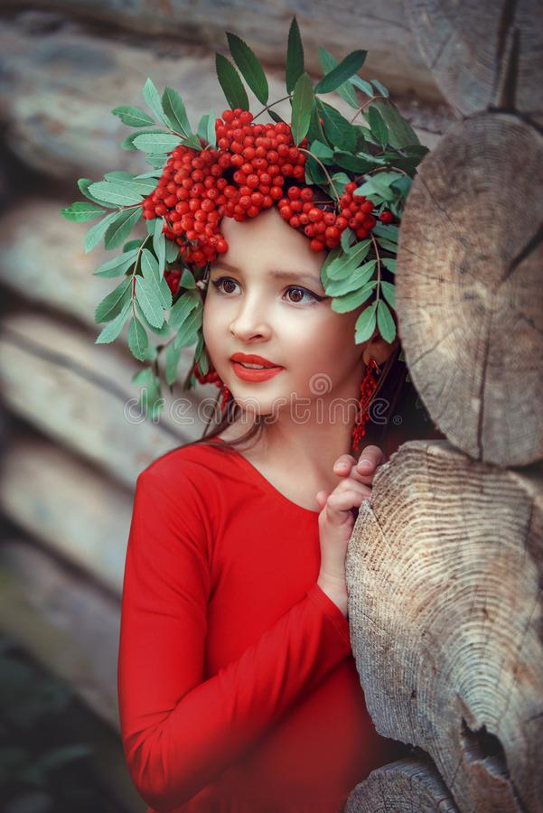 Little girl in the red dress with the mountain ash wreath. Near the wooden house royalty free stock photo