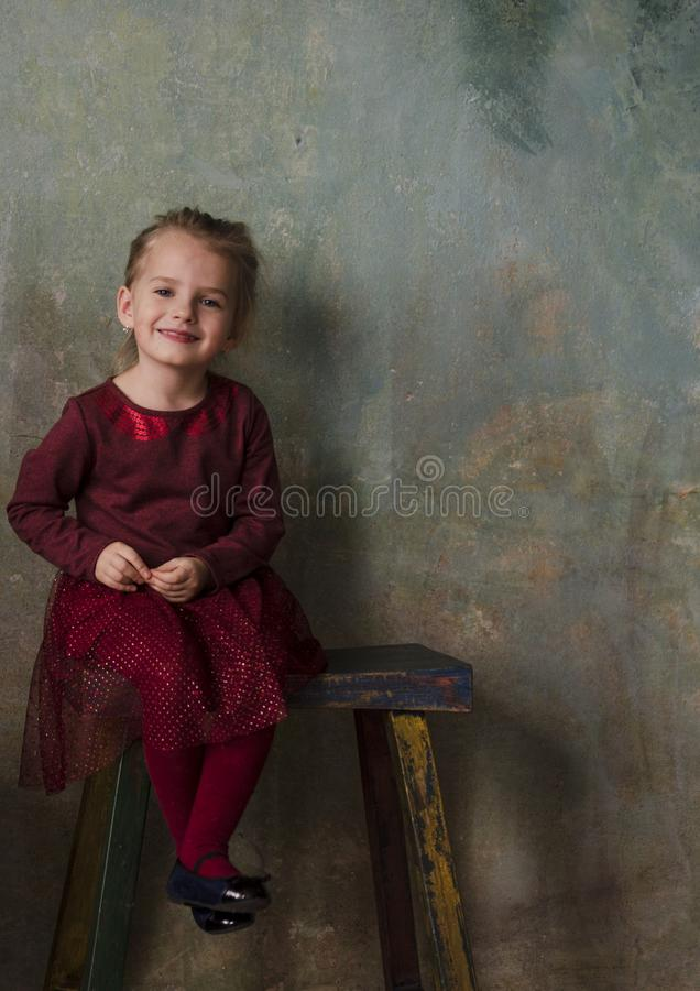 Little girl in red dress sitting on wooden stair and smiling royalty free stock image