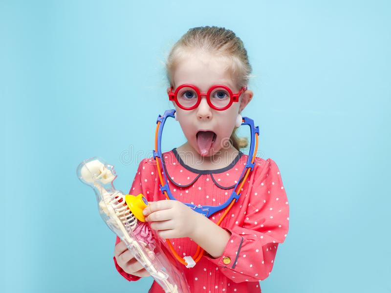 Little girl with red glasses listen heart with stethoscope. Little funny blonde girl with red glasses listen heart with stethoscope. The skeleton of a man with royalty free stock image