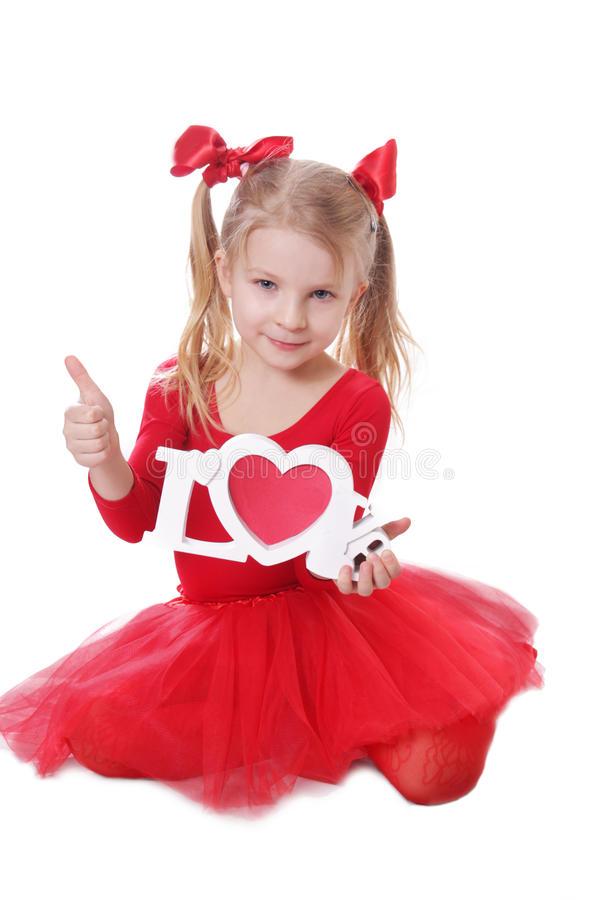 Little girl in red holding love words on white. Cute little girl in red holding love words on white royalty free stock photo