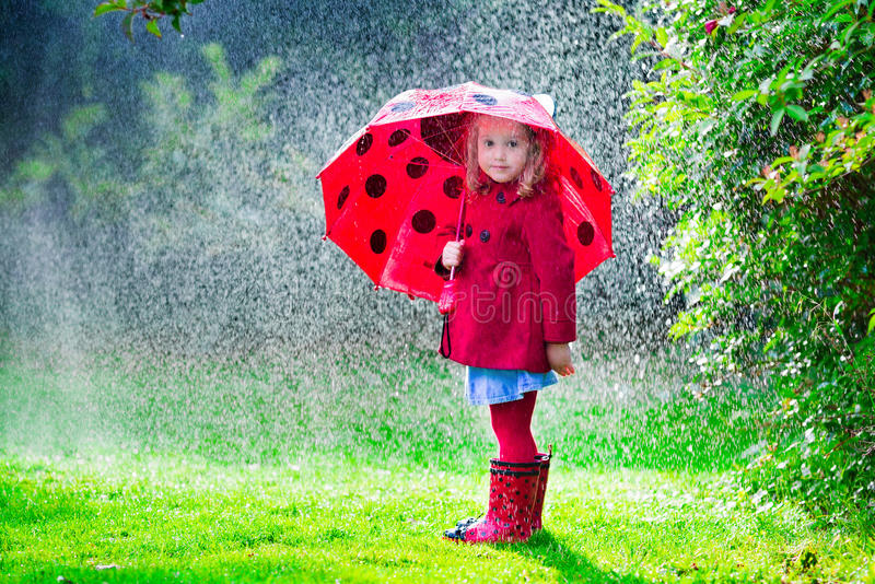 Little girl in red jacket playing in autumn rain. Little girl with red umbrella playing in the rain. Kids play outdoors by rainy weather in fall. Autumn outdoor royalty free stock images