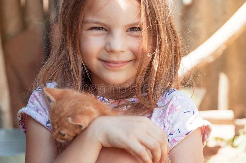 Little girl with a red kitten in hands close up. Bestfriends. I royalty free stock image